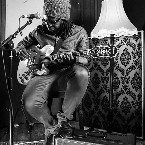 Mide With Guitar In Black And White In Front Of Lamp