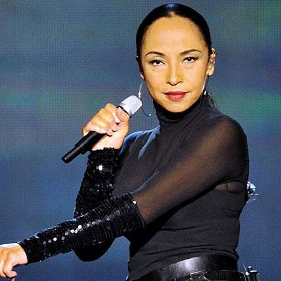 sade-slicked-back-hair-black-outfit-performing