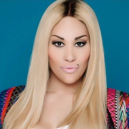 Keke-Wyatt-Blonde-Hair-Multicolored-Sweater-Blue-Background