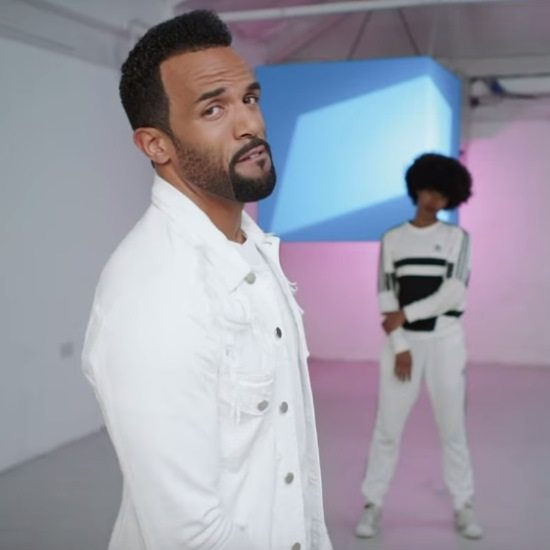craig-david-white-aint-giving-up-music-video-denim-jacket-blue-square-background-dancer-curly-fro
